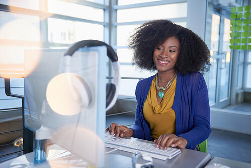 Portrait of a smiling woman with an afro at the computer in bright glass office-2